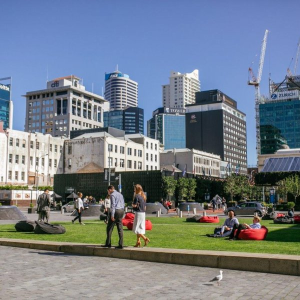 People walking through and sitting in Britomart's Takutai Square in Auckland's city centre, with cranes visible in the background. Image: Sacha Stejko.