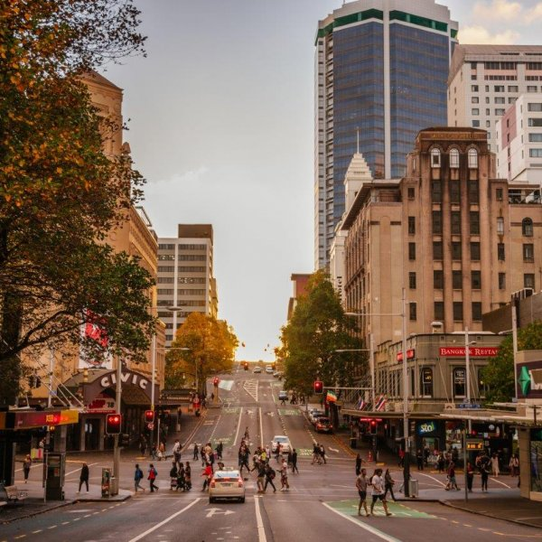 People crossing at the intersection of Queen and Wellesley Streets in Auckland's city centre - looking west towards the sun setting on the horizon. Image: Sacha Stejko.