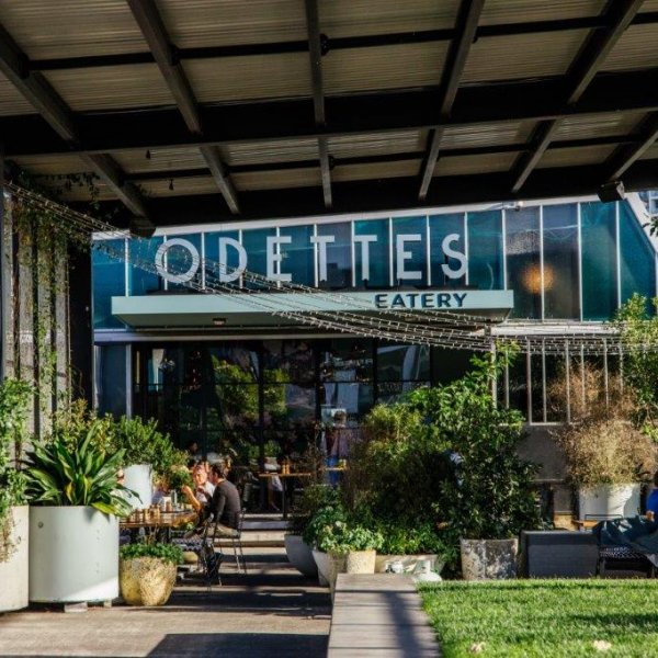 Odettes Cafe in CityWorks Depot in the sun surrounded by green space, diners, and sheltered seating