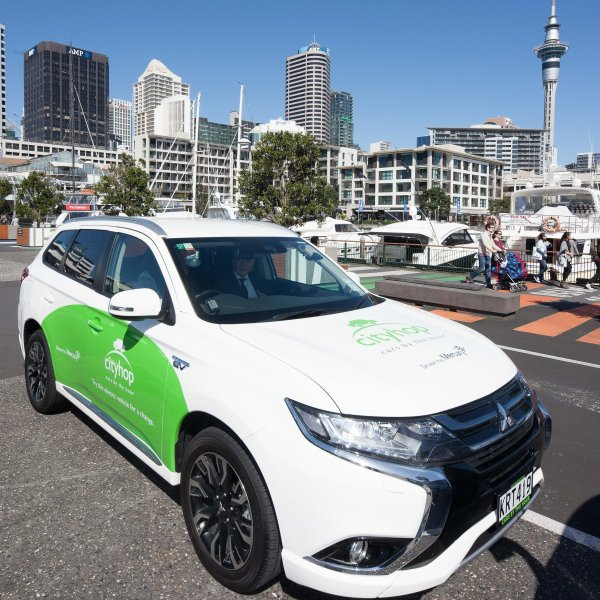 Cityhop car share on Auckland City Centres viaduct with view of skytower, tower blocks, water, boats, pedestrians, and restaurants