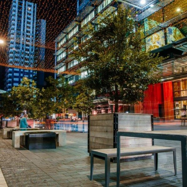 Federal Street at night in Auckland City Centre, SkyCity Convention Centre and restaurants alone the laneway with outdoor seating and dining, traffic, fairy lights, and tower blocks