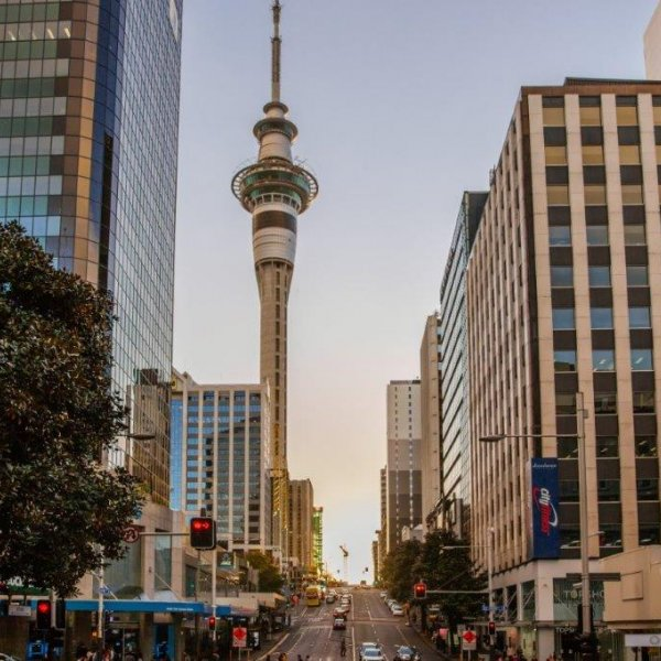 Victoria Street East looking passed the Queen Street intersection towards Victoria Street West, bank, retail and cafe in view with trees and greenery with SkyTower being lit by the sun, traffic, heritage buildings
