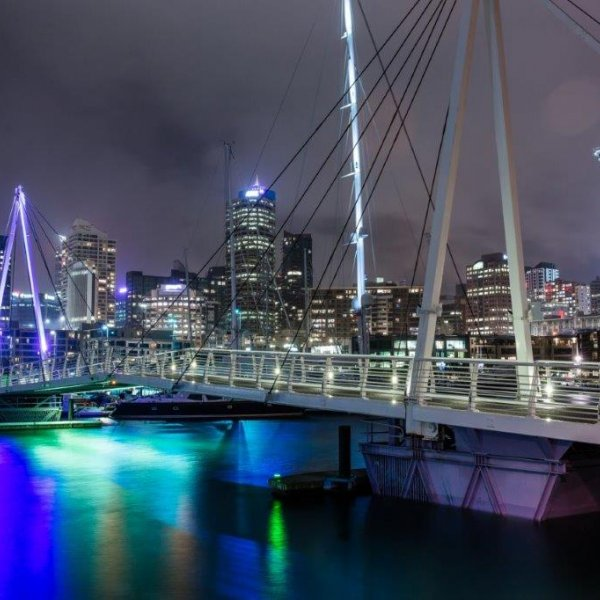 Wynyard Crossing bridge lit up at night above the water with views of yachts and boats in the harbour and the Sky Tower and sky scrapers lit up