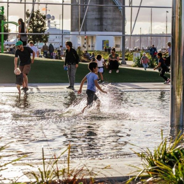 Children playing in water with parents and families at Silo Park, surrounded by art, gardens, greenery, trees, Wynyard Quarter silo's
