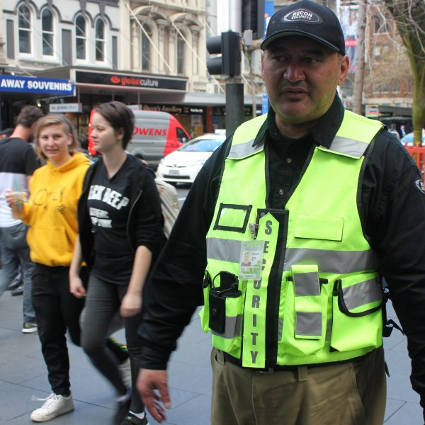 CityWatch team member JR John on Queen Street in Auckland City Centre among pedestrians, retail, green spaces, tourists, heritage buildings,