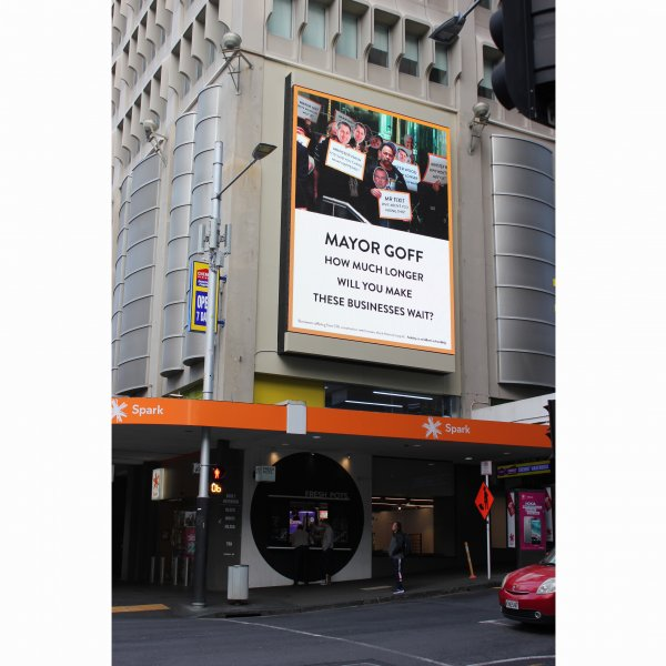A large billboard on a building at the corner of Queen and Wyndham Streets, with the text 'Mayor Goff: how much longer will you make these businesses wait?'. Above the text is a photograph of business owners gathering in protest with signs.