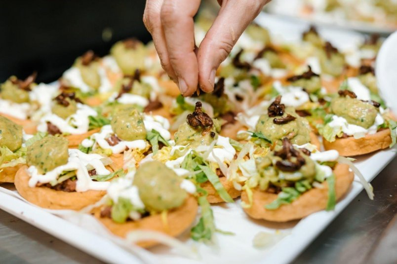 Feed Me Loco at Besos Latinos for American Express Restaurant Month 2018. Artisanal ground maize corncake topped with refried beans, lettuce, sour cream, guacamole and roasted crickets. Image: Sacha Stejko