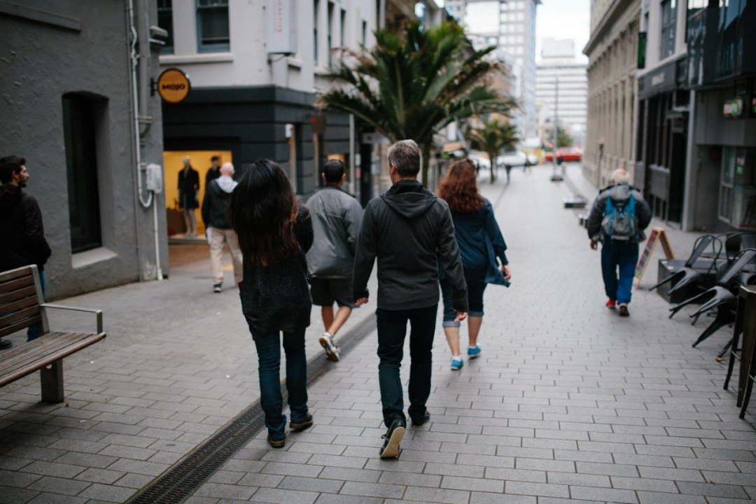 People walking in the O'Connell Street shared space in Auckland's city centre, with a Nikau palm and Mojo coffee sign in the background. Image: Sacha Stejko.
