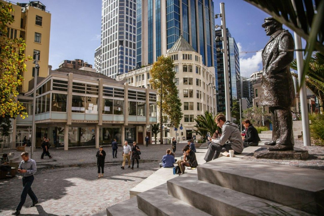 People sitting in the sun on the terracing in Freyberg Place in Auckland's city centre, with the statue of General Freyberg and the Ellen Melville Centre visible. Image: Sacha Stejko