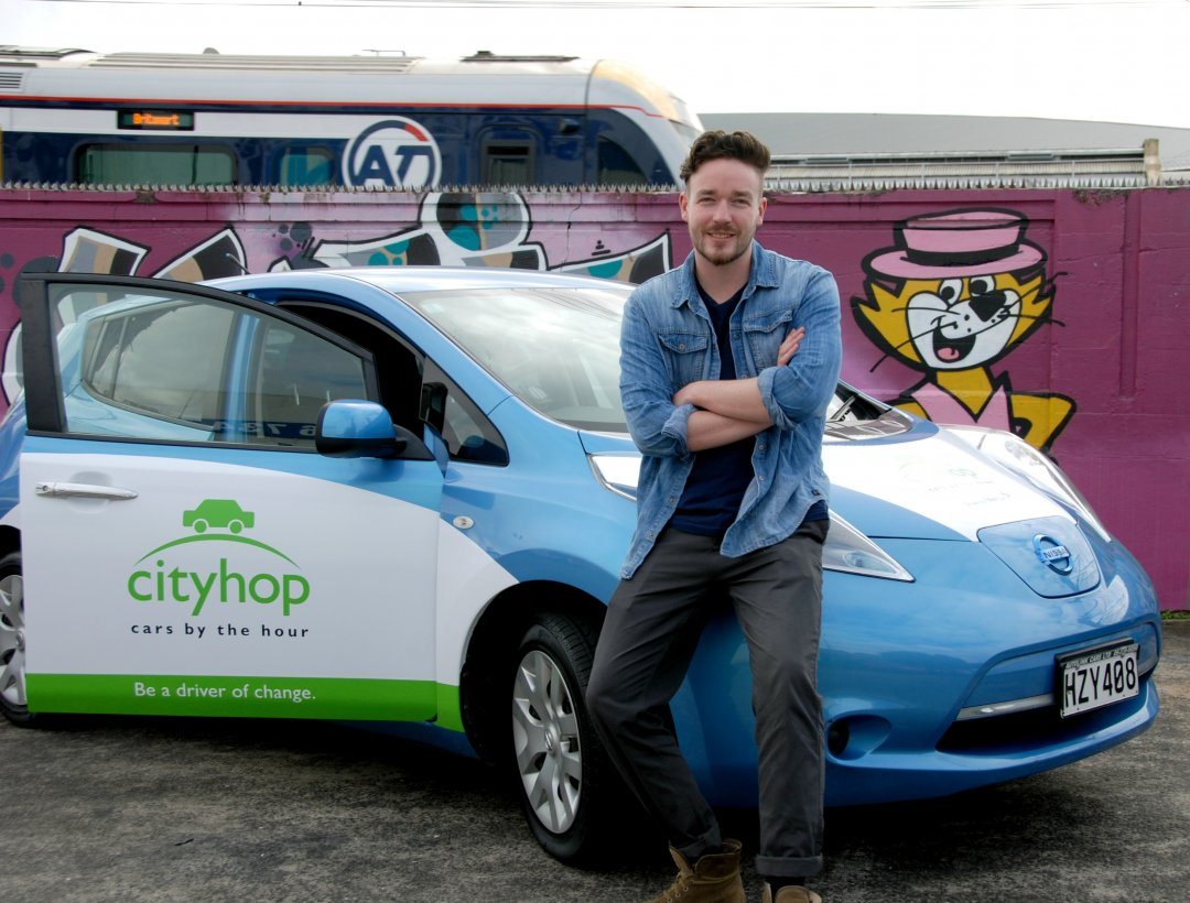 Cityhop General Manager Ben Carter with a Nissan Leaf EV from their fleet. Image: Cityhop.